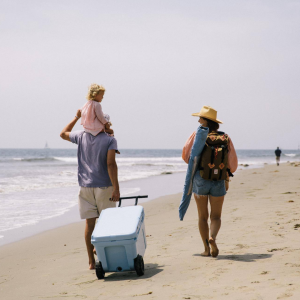 10% off coolers ad featuring a family walking on the beach dragging a blue cooler with them.