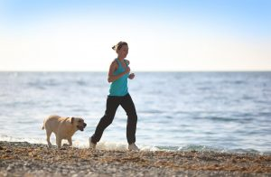 Picture for August Astro Sale used is Woman and dog pictured jogging on a beach